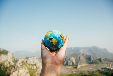 Person holding world globe facing mountain (Photo by Porapak Apichodilok from Pexels)